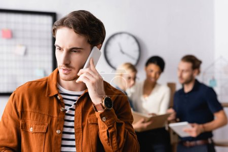 young businessman talking on smartphone near multiethnic businesspeople talking on blurred background