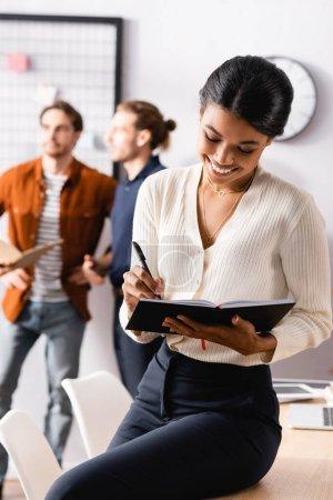 Photo pour Joyeuse femme d'affaires afro-américaine regardant dans un carnet tandis que ses collègues parlent sur fond flou - image libre de droit
