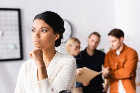 Photo pour Chère femme d'affaires afro-américaine détournant les yeux tandis que les gestionnaires multiethniques parlant sur fond flou - image libre de droit