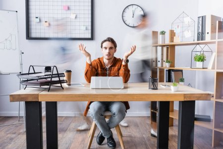 Photo for Confused businessman showing shrug gesture while sitting at desk in open space office, motion blur - Royalty Free Image
