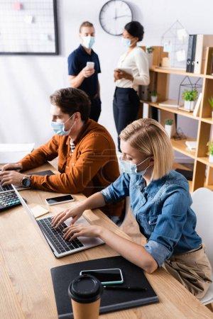 Manager in medizinischen Masken arbeiten an Laptops neben multikulturellen Kollegen, die vor verschwommenem Hintergrund sprechen