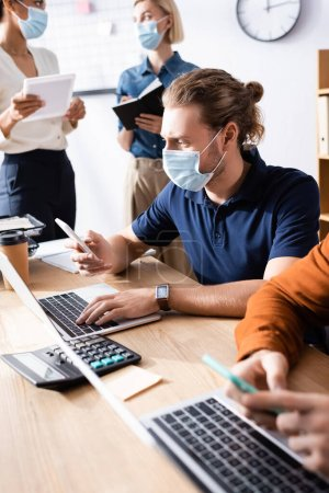 Photo for Young team of multicultural businesspeople in medical masks working together in open space office - Royalty Free Image