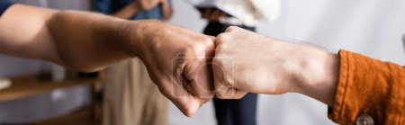 Photo for Partial view of businessmen doing fist bump near colleagues on blurred background, banner - Royalty Free Image
