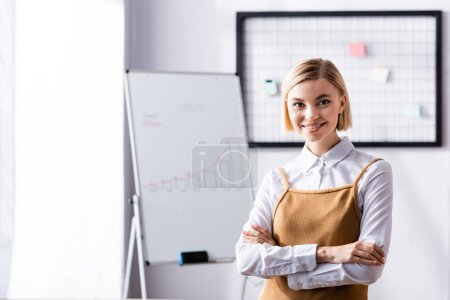 happy, blonde businesswoman looking at camera while standing with crossed arms