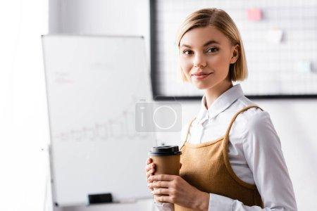 feliz mujer de negocios mirando a la cámara mientras sostiene el café para ir
