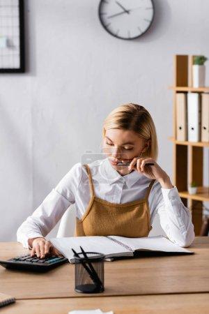Photo pour Comptable sérieux à l'aide d'une calculatrice près d'un ordinateur portable au premier plan flou - image libre de droit