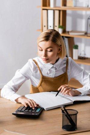 Photo pour Jeune, comptable concentré travaillant avec calculatrice près carnet vierge - image libre de droit