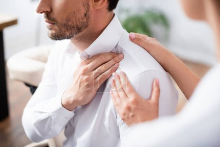 Photo for Cropped view of masseuse touching painful shoulder of businessman in office on blurred foreground - Royalty Free Image
