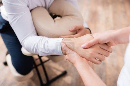 Photo pour Vue recadrée de masseuse faisant massage de la main de l'homme d'affaires sur fond flou - image libre de droit