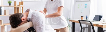 Female massage therapist massaging back of businessman sitting on massage chair in office, banner
