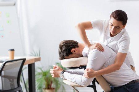 Photo pour Masseuse positive faisant massage des bras pour homme d'affaires au bureau sur fond flou - image libre de droit