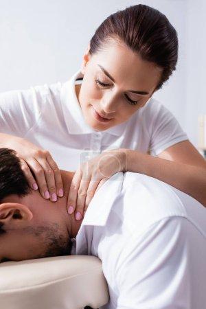 Vista de cerca de masajista positivo haciendo masaje de cuello para el cliente