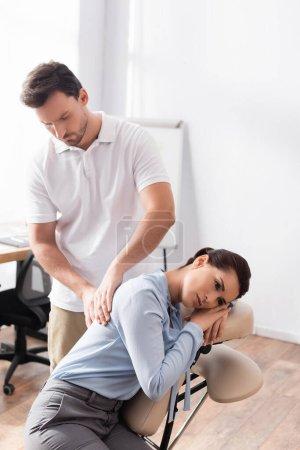 Photo pour Massothérapeute massant dos de femme d'affaires assise sur une chaise de massage au bureau sur fond flou - image libre de droit