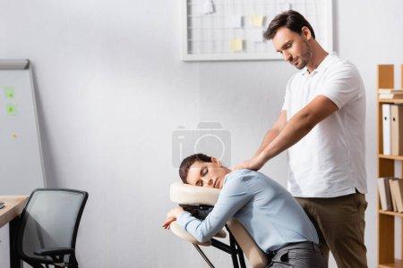 Photo pour Masseur souriant aux mains tendues massant les épaules d'une femme brune assise sur une chaise de massage au bureau - image libre de droit