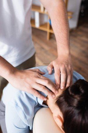 Photo pour Vue recadrée du masseur faisant massage assis du cou pour femme brune avec bureau flou sur fond - image libre de droit