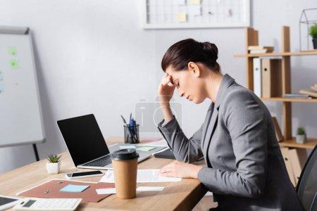 Foto de Mujer de negocios cansada con la mano en la frente sentada en el escritorio cerca de la computadora portátil y contrato en la oficina - Imagen libre de derechos