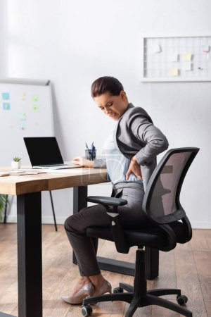 Exhausted businesswoman with hurting back holding hand on hip, while sitting on office chair in office