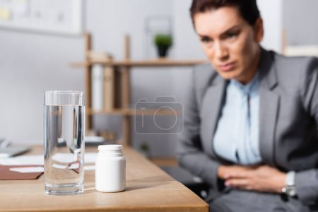 Photo for Glass of water and medication on desk with blurred businesswoman with stomachache on background - Royalty Free Image