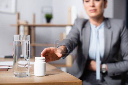 Photo for Cropped view of businesswoman with stomachache taking medication on blurred background - Royalty Free Image
