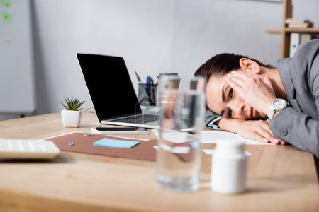 Photo for Businesswoman with migraine leaning on desk with laptop in office on blurred foreground - Royalty Free Image