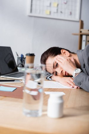 Photo for Exhausted businesswoman with headache leaning on desk with contract and laptop on blurred foreground - Royalty Free Image