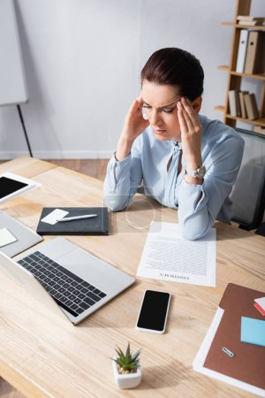 Female office worker with headache sitting at workplace with business document and digital devices in office