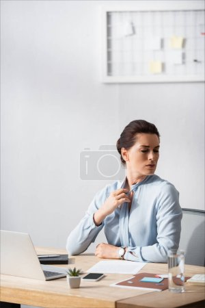 Photo for Businesswoman with painful neck untying blouse, while sitting at workplace on blurred background - Royalty Free Image
