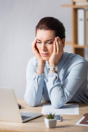 Foto de Cansada morena empresaria con dolor de cabeza apoyada en el lugar de trabajo sobre fondo borroso - Imagen libre de derechos