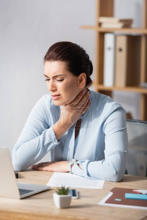 Photo for Brunette businesswoman with hand on painful neck sitting at workplace on blurred background - Royalty Free Image