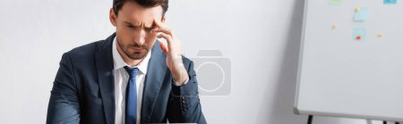 Tired businessman with headache, holding hand near temple and looking away with blurred flipchart on background, banner