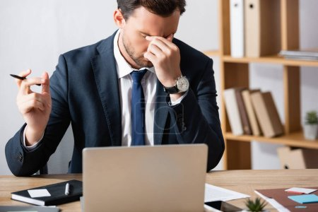 Tired businessman with migraine, holding hand near eyes, while sitting at workplace on blurred background