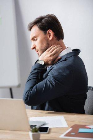 Photo pour Vue latérale de l'homme d'affaires avec le cou douloureux assis sur le lieu de travail sur fond flou - image libre de droit
