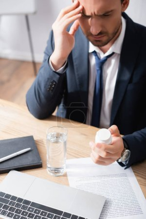 Photo for Businessman with migraine looking at medication, while sitting at workplace on blurred background - Royalty Free Image