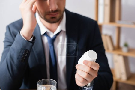 Photo for Cropped view of businessman holding medication near glass of water on blurred background - Royalty Free Image