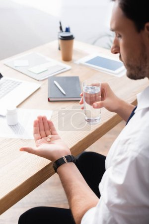 Photo for Businessman holding glass of water and looking at pills on palm, while sitting at workplace on blurred background - Royalty Free Image