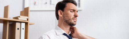 Businessman holding hand on aching neck, while looking away in office, banner