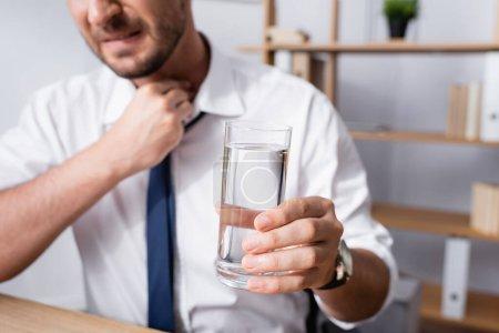 Photo pour Vue recadrée d'un homme d'affaires avec la main sur le cou, tenant un verre d'eau, assis sur le lieu de travail sur un fond flou - image libre de droit