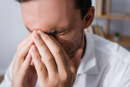 Close up view of exhausted office worker with migraine, holding hands near closed eyes on blurred background