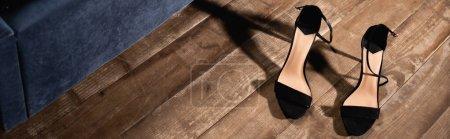 Black high heeled shoes on wooden floor, banner