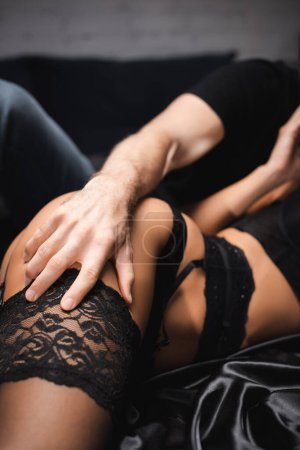 Photo for Cropped view of man touching stocking of sensual woman on satin bedding - Royalty Free Image