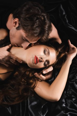 Photo for Top view of passionate man kissing and touching neck of sensual woman with red lips on black bedding - Royalty Free Image