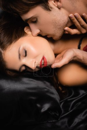 Young man kissing sexy girlfriend with red lips on black satin bedding