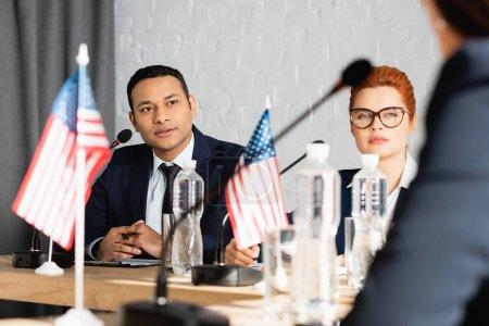 Photo pour Des politiciens interraciaux focalisés regardant une collègue alors qu'elle était assise dans une salle de conférence sur un premier plan flou - image libre de droit