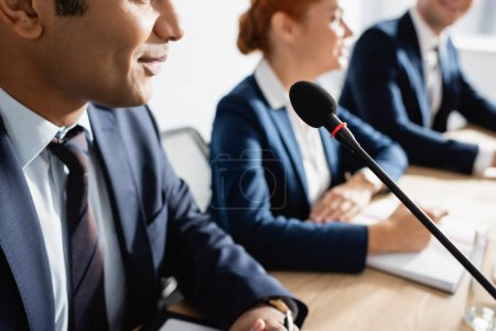 Photo for Positive indian politician sitting near microphone with blurred colleagues on background - Royalty Free Image