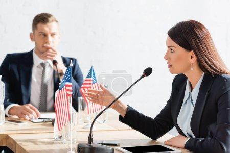 Photo pour Femme brune gestuelle, tout en parlant au microphone, assise près d'une tablette numérique avec un homme flou en arrière-plan - image libre de droit