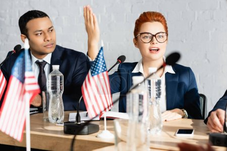 Indian politician looking at redhead woman with raised hand, while talking in boardroom on blurred foreground
