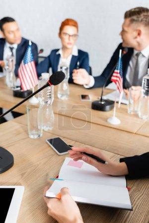 Female politician with pen and notebook sitting near smartphone and microphone with blurred colleagues working on background