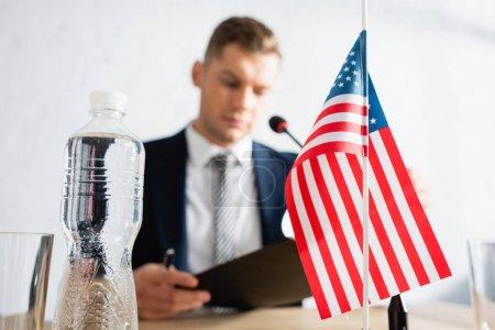Photo pour Bouteille d'eau et petit drapeau américain sur la table avec politicien flou sur le fond - image libre de droit