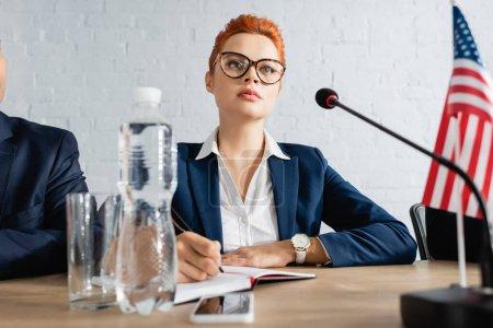 Photo pour Femme concentrée écrivant dans un cahier, alors qu'elle était assise près d'un collègue dans une salle de conférence pendant une réunion d'un parti politique - image libre de droit