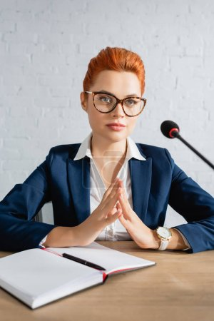 Focused redhead woman fingertips touching gesture, looking away, while sitting at table in boardroom
